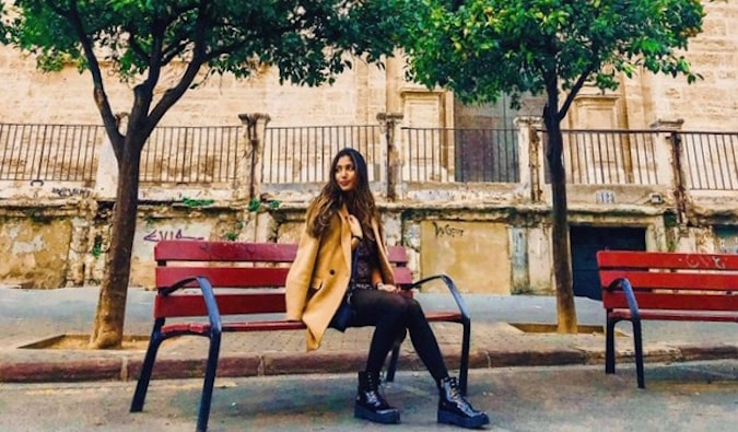 Natasha, a solo female traveler and English teacher in Spain sitting on a bench