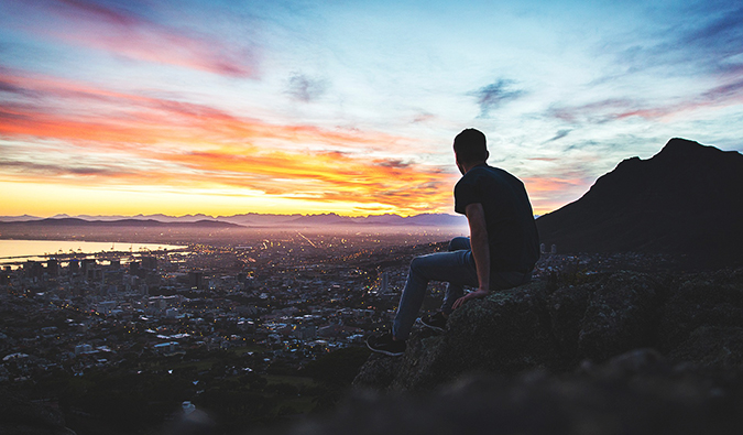 a man gazing out over a city landscape at sunset