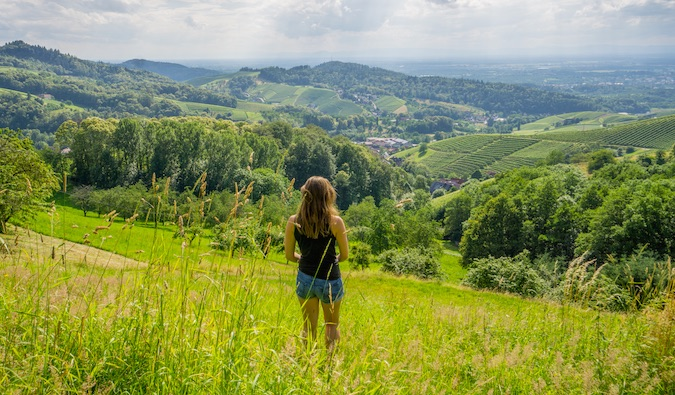 Kristin Addis standing in a green field with views of rolling hills