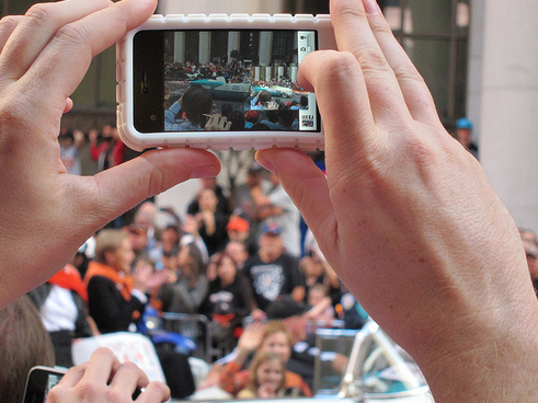 A fan snaps a photo during the parade for the San Francisco Giants
