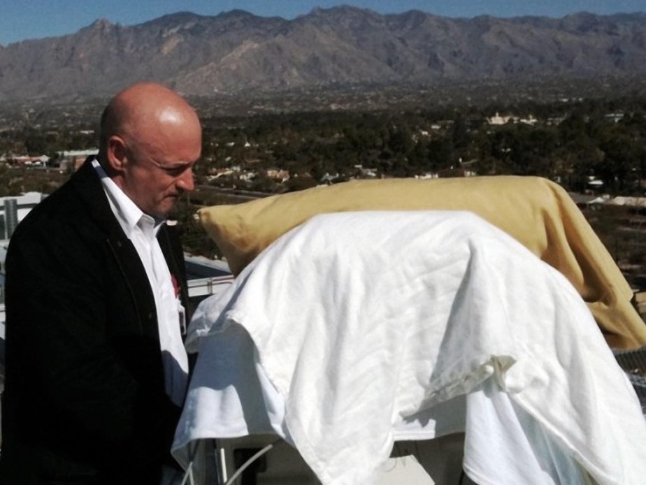 In this photo provided by the office of Rep Gabrielle Giffords, Giffords' husband, Mark Kelly, stands with his wife as she looks from her bed at the Santa Catalina Mountains while on an outdoor deck at University Medical Center in Tucson, Ariz., Thursday, Jan. 20, 2011.