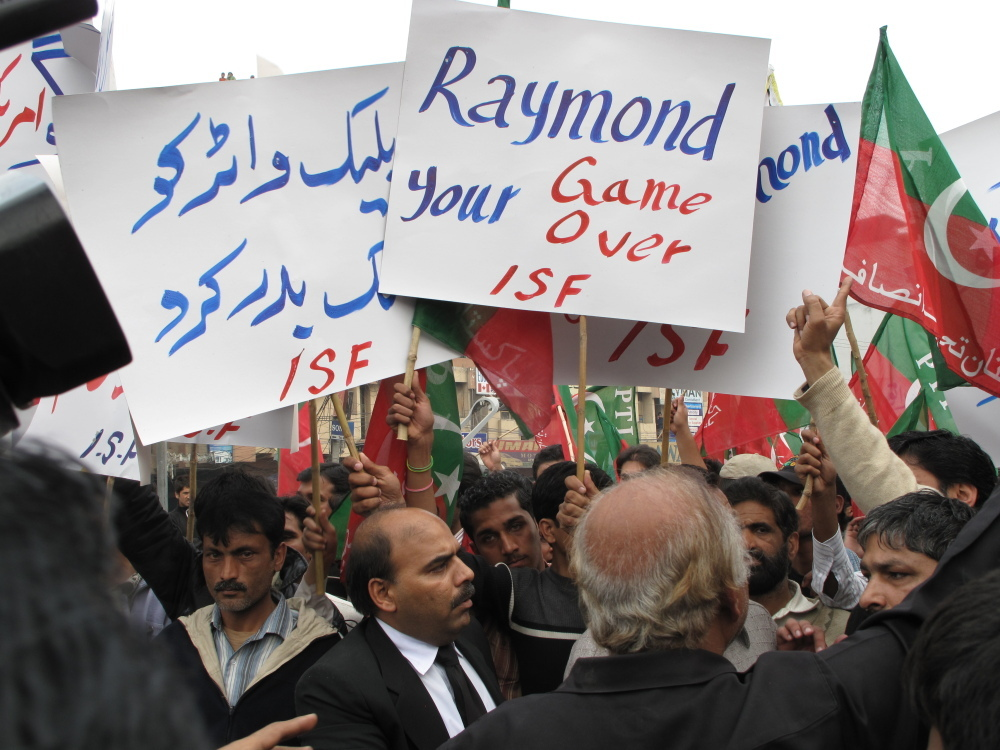 "A small but vocal crowd gathered as a Magistrate Court in Lahore decreed that Pakistani authorities may continue to hold the U.S. diplomat identified as Raymond Davis, alleged to have shot dead two Pakistani men. Protesters shouted ""Hang Davis!"" while the U.S. Embassy cried foul.  It called his detention ""illegal"" and said the  hearing itself violated his right to due process."