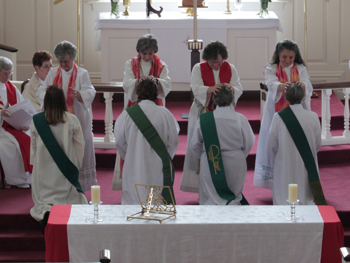 "The ""Laying On Of Hands"" during the ordination ceremony. The priests lay hands on the candidates, invoking the Holy Spirit, before they are officially ordained. They are, left to right: Ann Penick, Marellen Mayers, Bishop Andrea  Johnson (center, performed the ordination), Patricia ""Patti"" LaRosa and  Caryl Johnson."