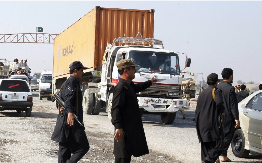 Pakistani security personnel stop trucks carrying supplies for NATO forces in neighboring Afghanistan at a checkpoint in Khyber, Pakistan, on Saturday. Islamabad closed the border crossing after NATO aircraft allegedly killed 24 Pakistani troops.