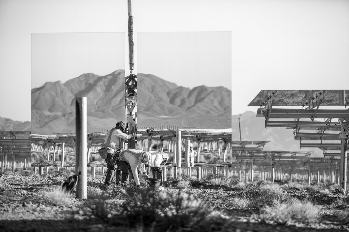 """Workers install a """"heliostat"""" — or a device with a mirror that reflects the sun, or in this case the nearby mountains. Background shows assembled heliostats in """"safe"""" or resting position. June 2012."""