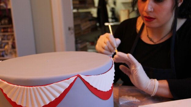 Elena Fox from Charm City Cakes works on a layer of the official cake for the Commander-in-Chief's Ball.