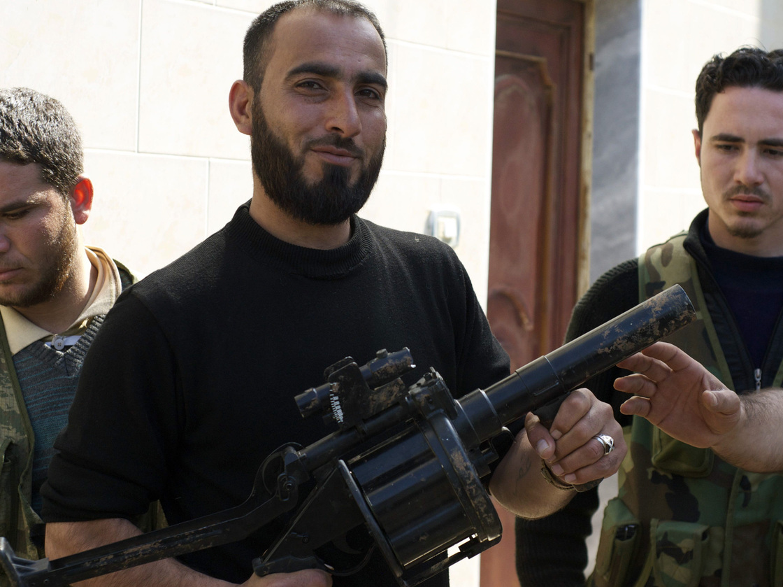 "A Syrian rebel in the city of Kfar Nbouda holds a grenade launcher in February, part of a recent weapons shipment to the rebels by the Saudi government. Arms are not the only thing flowing from Saudi Arabia to Syria. Young Saudis are joining Islamist rebels in a ""holy war"" against President Bashar Assad."
