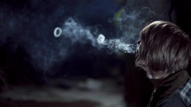 A human blowing smoke rings.