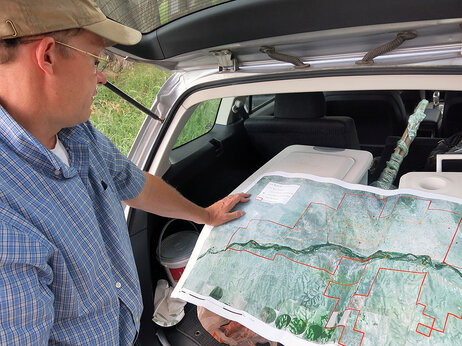 Ecologist William Burnidge checks a map of Fox Ranch that details the different areas rancher Nathan Andrews can graze his cattle.