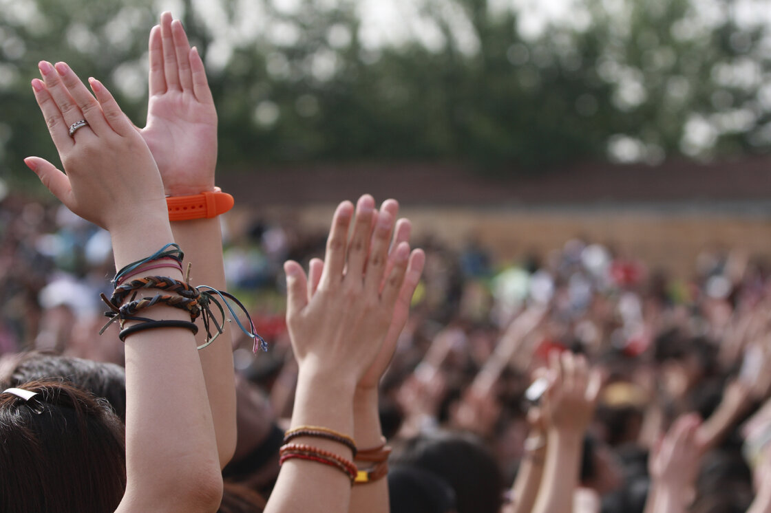 Hands raised up high, clapping at a concert.