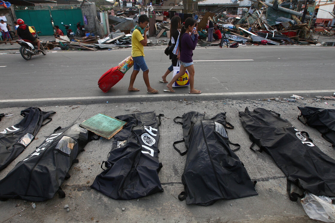 People cover their noses from the stench of dead bodies in Tacloban. As of late Wednesday morning in the U.S., the official death toll stood at more than 2,300.