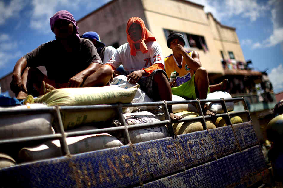 Men ride on top of a truck carrying food aid.