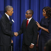 President Barack Obama and first lady Michelle Obama shake hands with college graduate Troy Simon, who couldn't read until he was 14. The president spoke about college opportunities in the Eisenhower Executive Office Building across from the White House on Thursday, Jan. 16, 2014.