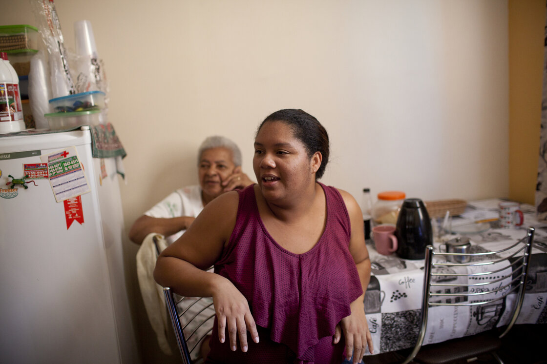 Jeane Tomas, with her mother, in their two-bedroom apartment, in Rio de Janeiro's far west zone of Campo Grande. The family was relocated to this area three years ago to make way for building projects related to the 2016 Summer Olympics in Rio.