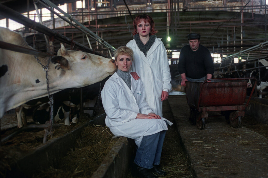 Marina, an insemination technician, and Lyuba, a milkmaid, pose for a portrait on a dairy farm south of St. Petersburg, near the road to Moscow.