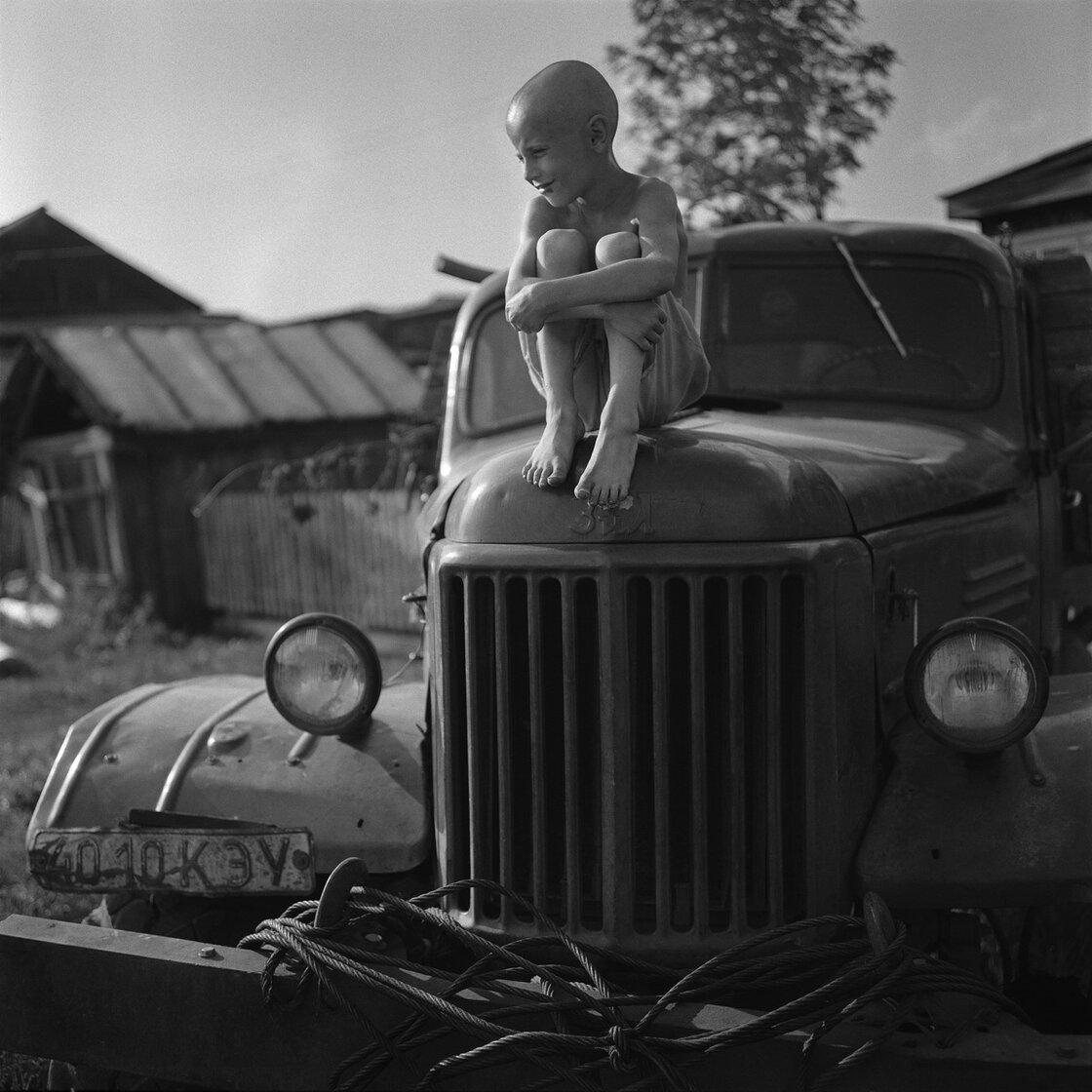 A boy named Zahar sits on an old car in a village called Rossiyka near Krasnoyarsk.