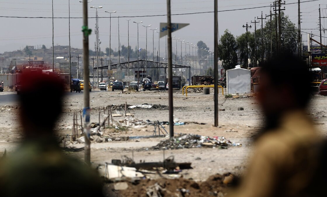 Kurdish peshmerga forces look at a checkpoint held by militants of the Islamic State of Iraq and Syria in Iraq's second city, Mosul, on Monday.