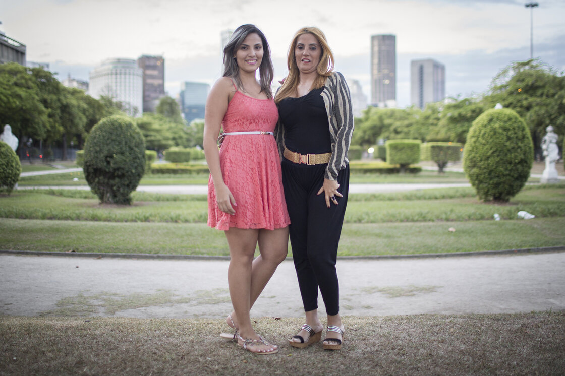 "Janet Timal, 47 (right), stands with her niece Thairine, 21. Janet has had a tummy tuck and breast augmentation and helped her niece pay for liposuction. ""The ideal is to be able to put something on, to sit down and not have your belly jumping out. Here in Brazil it gets hot, and the less clothes, the better,"" says Janet."