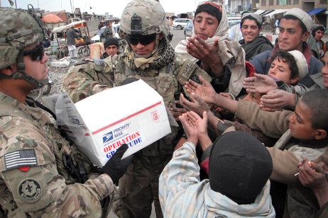Troops in Afghanistan pass out candy that was collected by dentists in the buyback program and shipped by Operation Gratitude.