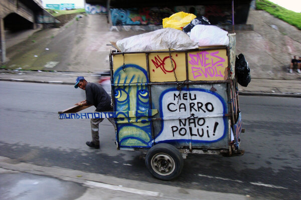 "A waste picker wheels a trash cart with Mundano's art and spreads the word: ""My cart doesn't pollute."""