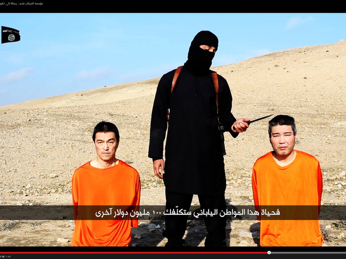 A photo from a video clip posted on YouTube shows a man with a knife threatening two captives identified as Haruna Yukawa (right) and Kenji Goto Jogo. The Islamic State says it wants $200 million for their release.