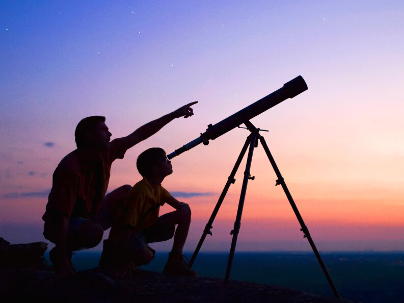 A boy and his dad look through a telescope.