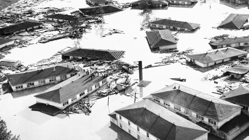 People stand marooned on housetops in the community of Vanport, Ore. on May 30, 1948 while water swirls through debris of their town.
