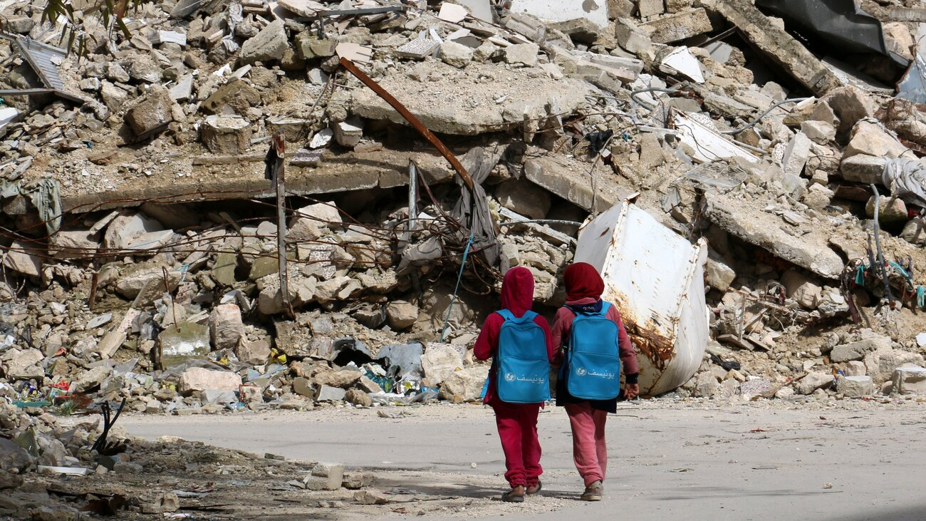 Syrian girls, carrying school bags provided by UNICEF, walk past the rubble of destroyed buildings on their way home from school on March 7 in the rebel-held al-Shaar neighborhood of Aleppo, Syria. So many people have fled the city and so much of its infrastructure has been destroyed that nighttime satellite images show 97 percent less light compared to four years ago.