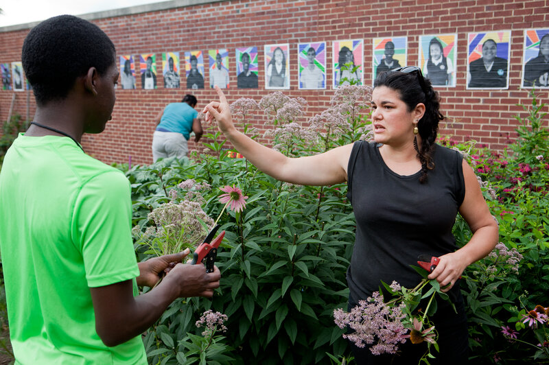 Rebecca Lemos-Otero (right), co-founder and co-executive director of City Blossoms, helps Erwin Tcheliebou, 15, pick flowers to sell at the farmers market. Behind her is a wall featuring the painted portraits of Eastern Senior High students who have worked in the garden.