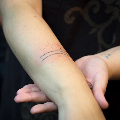 Holly Mititquq Nordlum shows off her partially completed tattoo during a live demonstration at Anchorage's Above The Rest studio. Nordlum's Inupiaq name, Mititquq, means a place where birds land, and she commemorates big life achievements with bird feet tattoos, like the two on her opposite wrist.