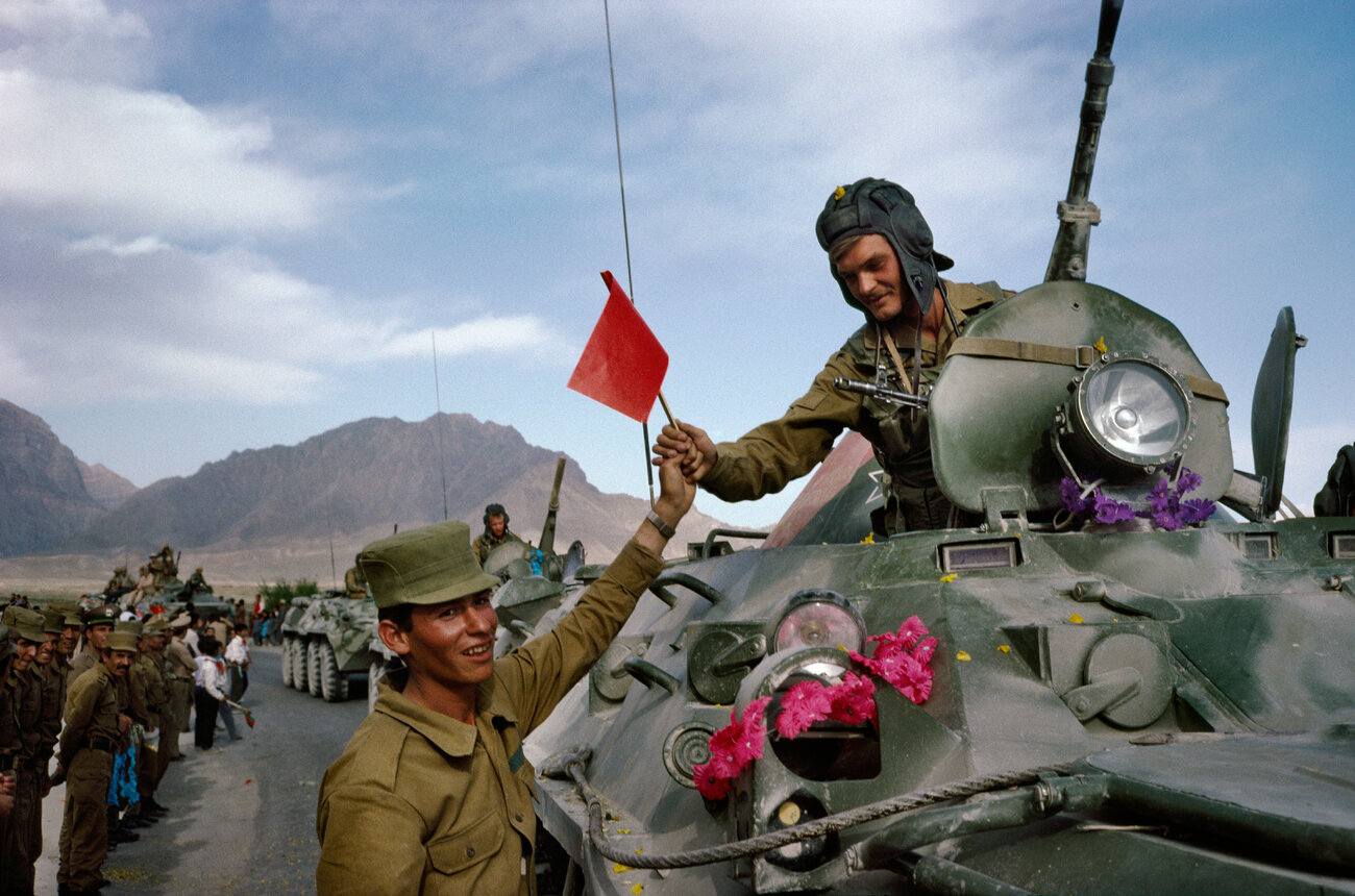 "On the first day of the Soviet withdrawal from Afghanistan in May 1988, an Afghan soldier hands a flag to a departing Soviet soldier in Kabul. ""This was the first time journalists had full access to Kabul,"" Robert Nickelsberg says. It marked his first year covering Afghanistan. ""It was a historical turning point for the Cold War and actually foreshadows the chaos that will descend on the country."""