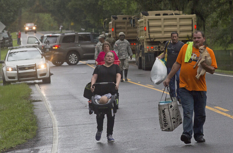 People are evacuated by members of the Louisiana Army National Guard near Walker, La., on Sunday.