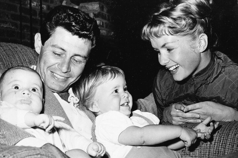 Singer Eddie Fisher and actress Debbie Reynolds cuddle their two children, four-month old Todd (left) and 19-month-old Carrie, in 1958.