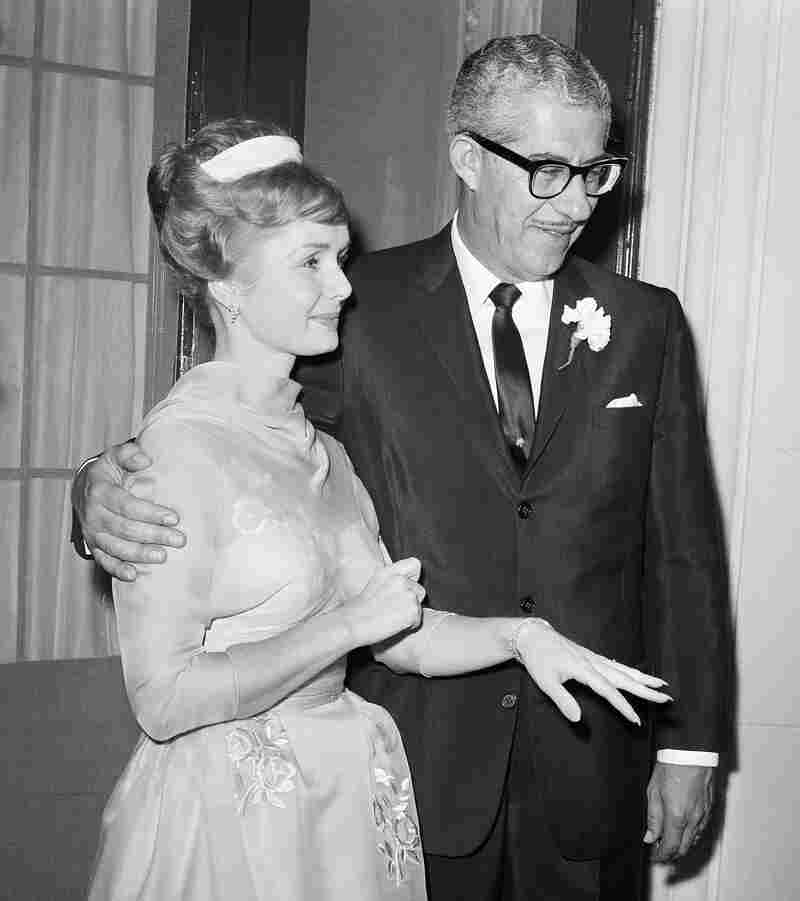 Debbie Reynolds holds out her hand to display her wedding ring as she stands beside multimillionaire shoe magnate Harry Karl following their wedding at Beverly Hills, Calif., in November 1960.