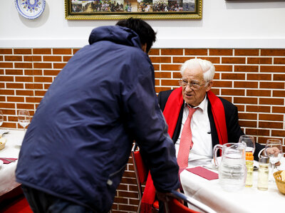 A dinner patron chats with Father Angel (right), who says that he wants homeless people to
