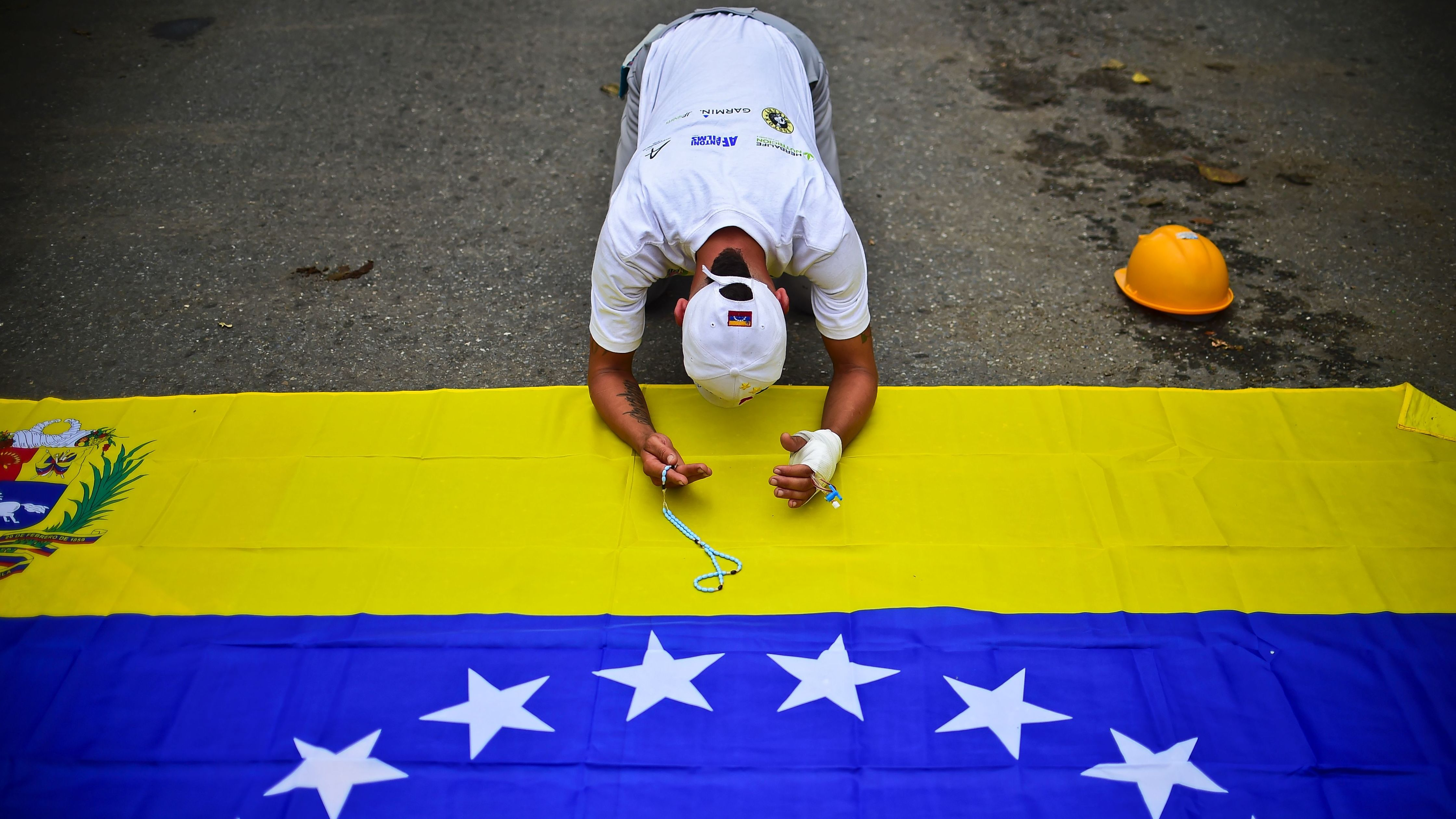 An opposition activist bows before the Venezuelan flag during a protest in Caracas on Monday.