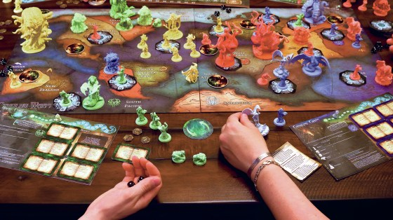 Four players sit around Cthulhu Wars, a game designed by Sandy Petersen, who also designed Call of Cthulhu.