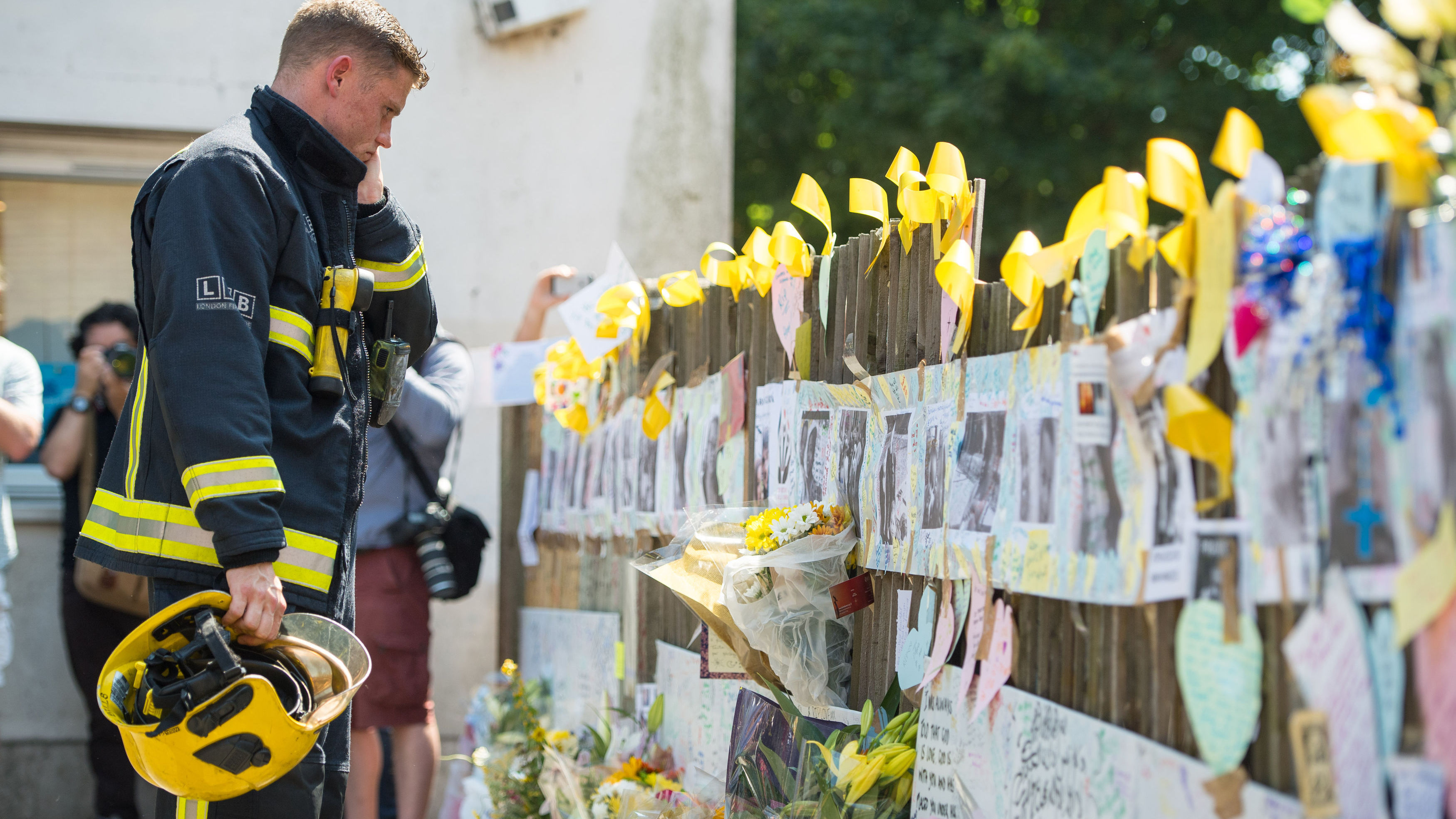 A firefighter looks at tributes to presumed victims of the Grenfell Tower fire, after observing a minute