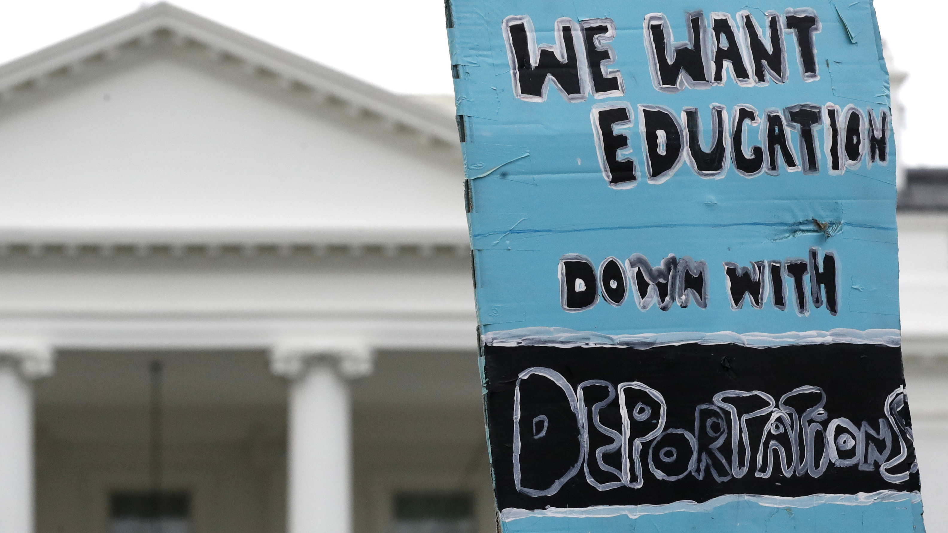 """A sign is held up by the White House in support of the DREAMers and the Deferred Action for Childhood Arrivals (DACA) program, on Sept. 5, when Attorney General Jeff Sessions announced the Trump administration will """"wind down"""" DACA."""