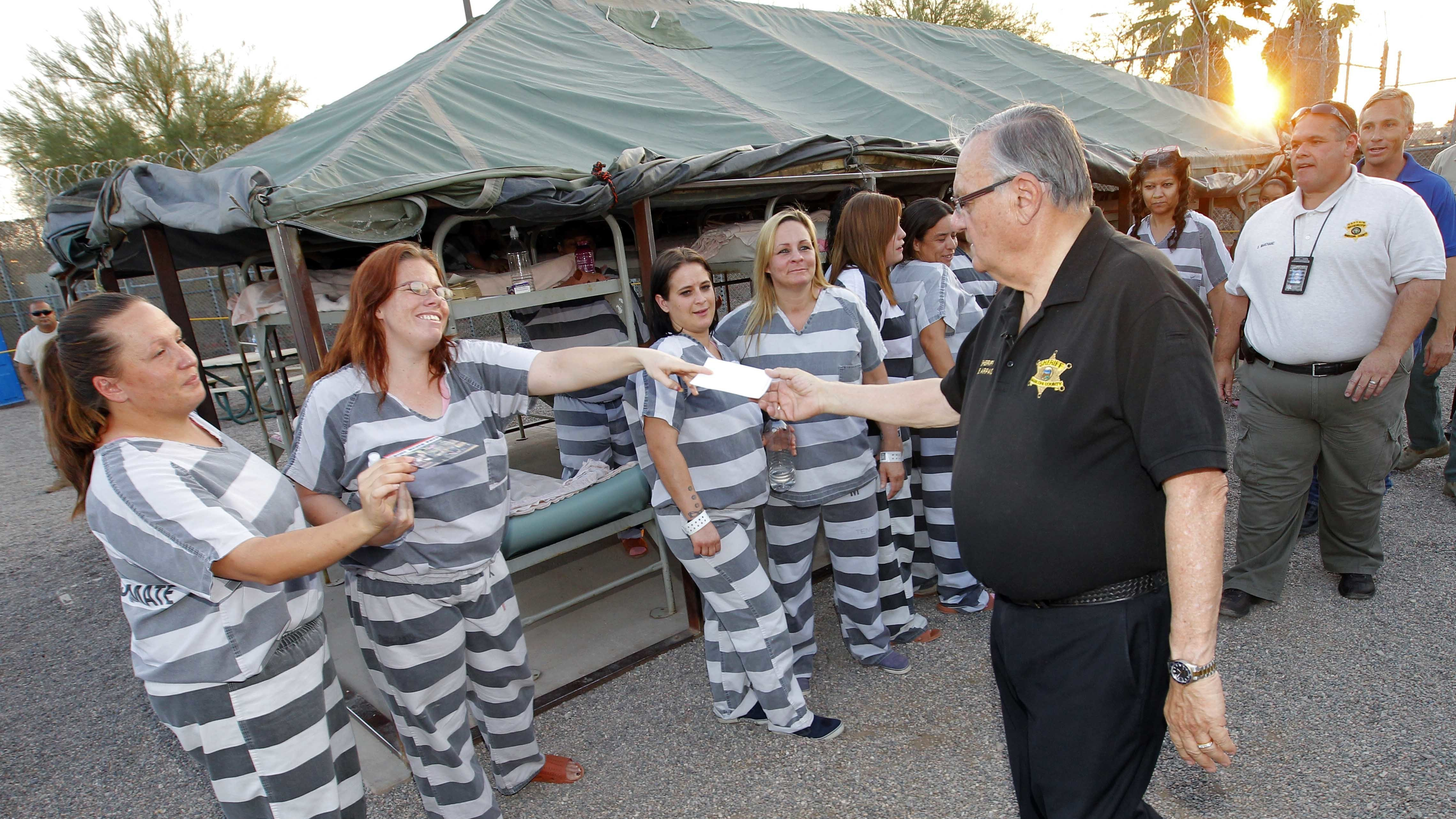 """Maricopa County Sheriff Joe Arpaio signs autographs for inmates as he walks through  """"Tent City"""" in Phoenix in 2012."""