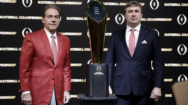 Alabama coach Nick Saban (left) and Georgia coach Kirby Smart pose with the NCAA college football championship trophy at a press conference in Atlanta.