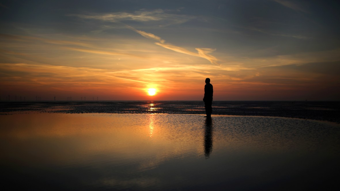 "One of the life-size body cast statues of ""Another Place"" created by the artist Antony Gormley looks out over the Mersey Estuary at sunset at Crosby beach on April 15, 2014, in Crosby, United Kingdom."
