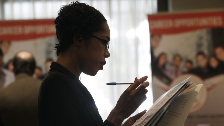 Joana Dudley looks at a list of job prospects at a job fair in Miami Lakes, Fla., in January. Economists say the government
