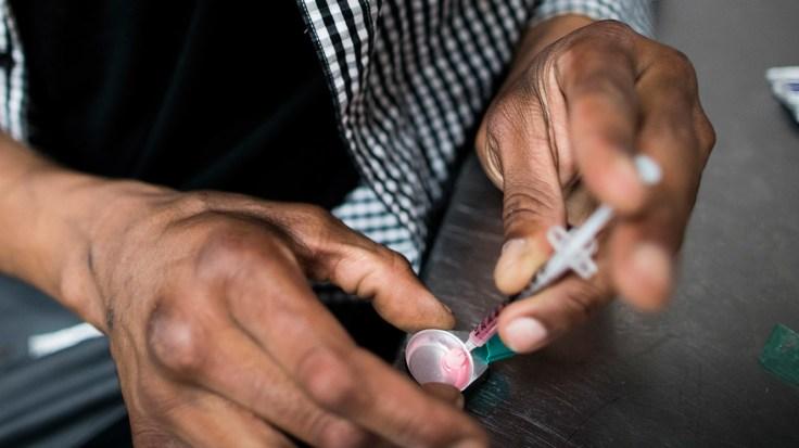 A drug user prepares a hit of heroin inside VANDU