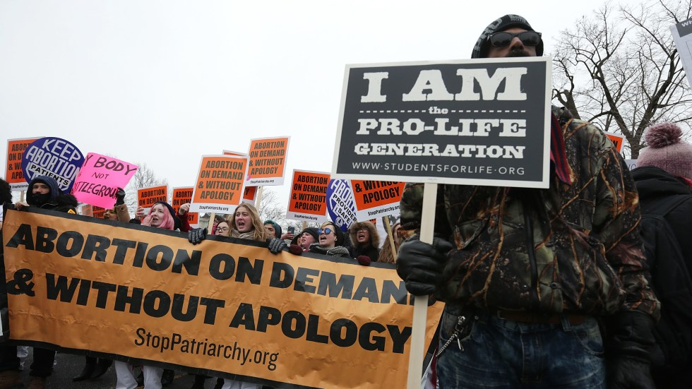 Protesters spread their dueling messages at a March for Life rally in 2016. Only 17 percent of Americans say they want the landmark Roe v. Wade ruling overturned, a new NPR/PBS NewsHour/Marist poll finds.