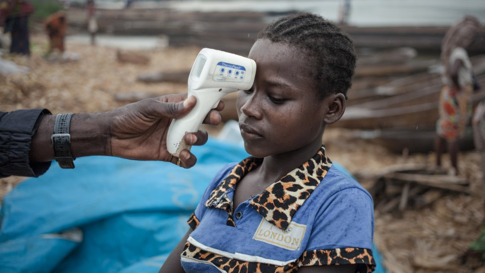 A health worker monitors the temperature of a traveler from the Democratic Republic of the Congo during the Ebola outbreak that ended in July. The virus has now surfaced in another part of the country.