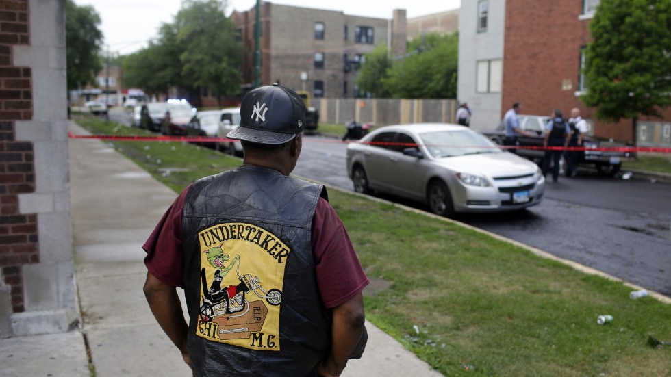 A bystander watches as Chicago police investigate a street where multiple people were shot on Sunday.