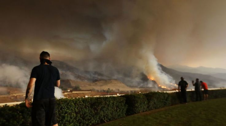 Resident Moe Blythe watches the Holy Fire burn near homes on August 9, 2018 in Corona, California.