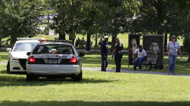 A police officer speaks to a man walking on New Haven Green, on Wednesday, in New Haven, Conn. More than 70 people fell ill from suspected drug overdoses on the green and were taken to local hospitals.