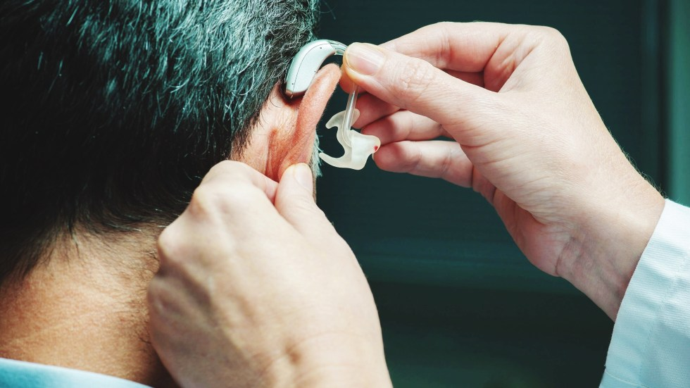 Man gets hearing aid adjusted. Studies found restoring hearing and vision can stave off cognitive decline.